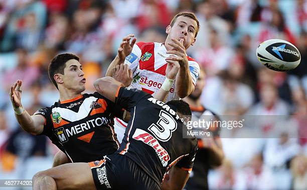 Adam Quinlan of the Dragons competes with Mitchell Moses of the Tigers for a high ball during the round 20 NRL match between the Wests Tigers and the...