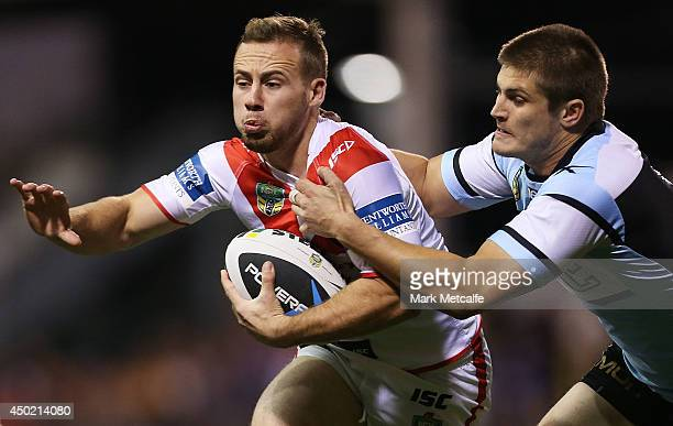 Adam Quinlan of the Dragons is tackled by Blake Ayshford of the Sharks during the round 13 NRL match between the St George Illawarra Dragons and the...