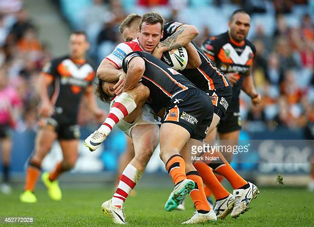 Adam Quinlan of the Dragons is tackled during the round 20 NRL match between the Wests Tigers and the St George Illawarra Dragons at ANZ Stadium on...
