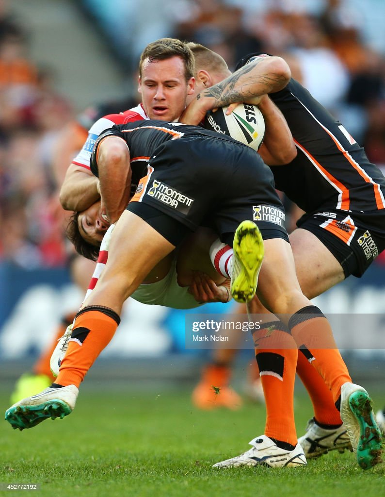 Adam Quinlan of the Dragons is tackled during the round 20 NRL match between the Wests Tigers and the St George Illawarra Dragons at ANZ Stadium on July 27, 2014 in Sydney, Australia.