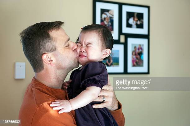 Adam Raines attempts to console Hannah 17months Sunday December 23 2012 in Westminster MD After a 2 1/2 year wait he and his wife just picked up...