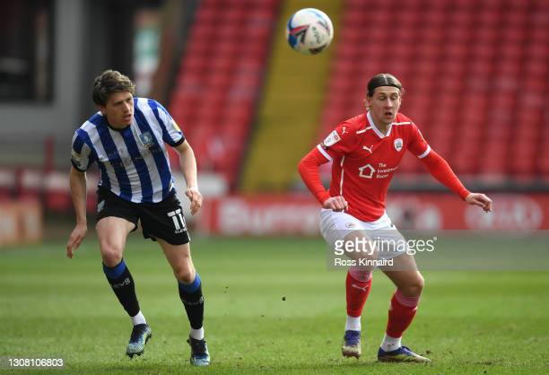 Adam Reach of Sheffield Wednesday and Callum Brittain of Barnsley FC battle for possession during the Sky Bet Championship match between Barnsley and...