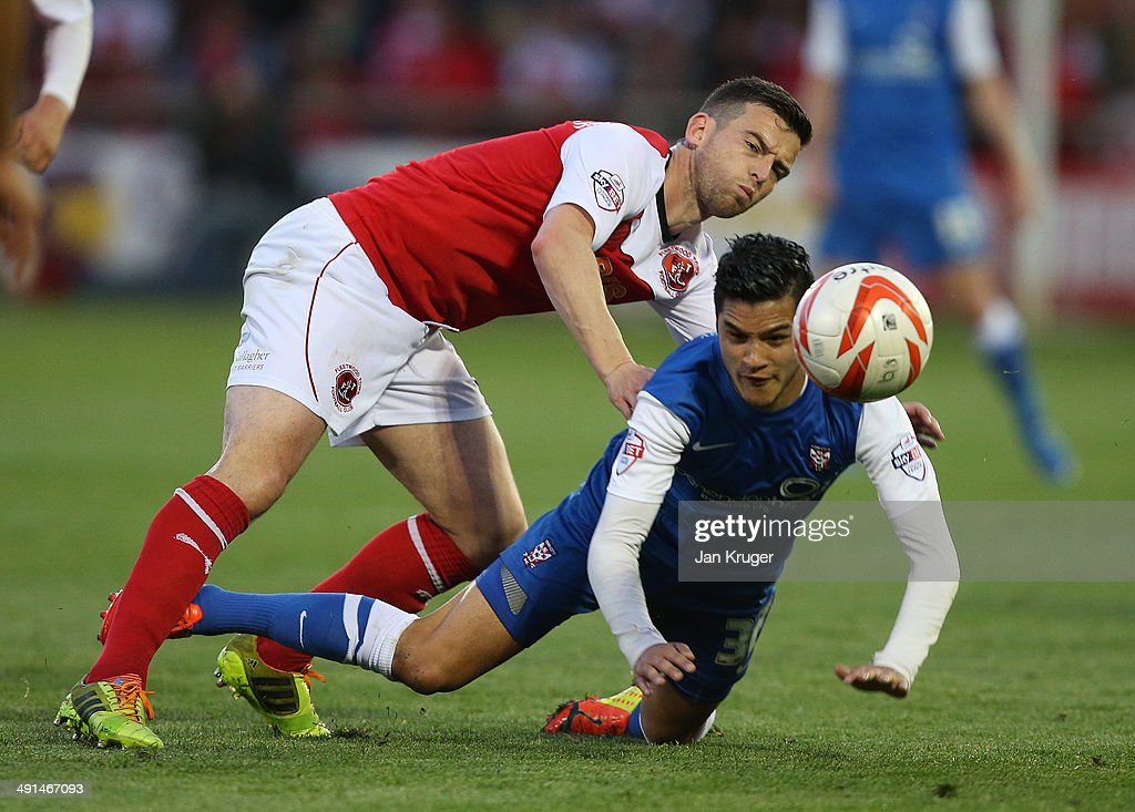 Adam Reed of York City is tackled by Steven Schumacher of Fleetwood Town during the Sky Bet League Two play off Semi Final second leg match between Fleetwood Town and York City at Highbury Stadium on May 16, 2014 in Fleetwood, England.