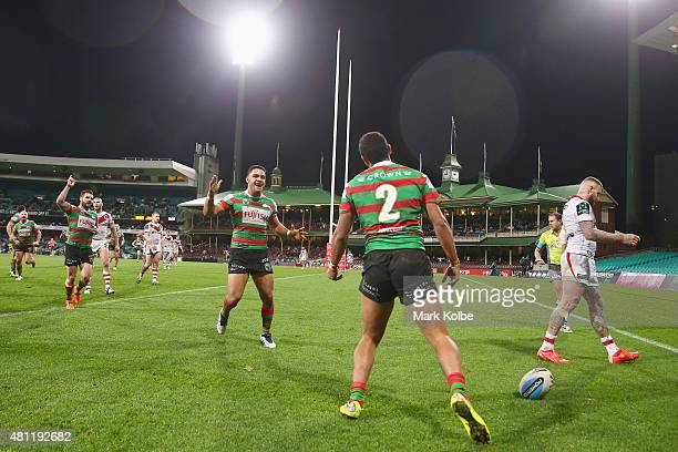 Adam Reynolds and Dylan Walker of the Rabbitohs run to congratulate Alex Johnston of the Rabbitohs as he celebrates scoring a try during the round 19...