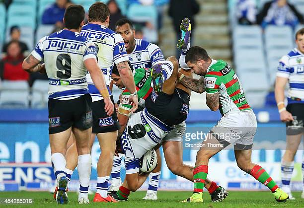 Adam Reynolds and Issac Luke of the Rabbitohs tackles Moses Mbye of the Bulldogs in a dangerous fashion during the round 25 NRL match between the...