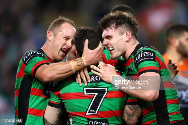 Adam Reynolds of the Rabbitohs celebrates scoring a try with Jason Clark and Angus Crichton of the Rabbitohs during the round 25 NRL match between...
