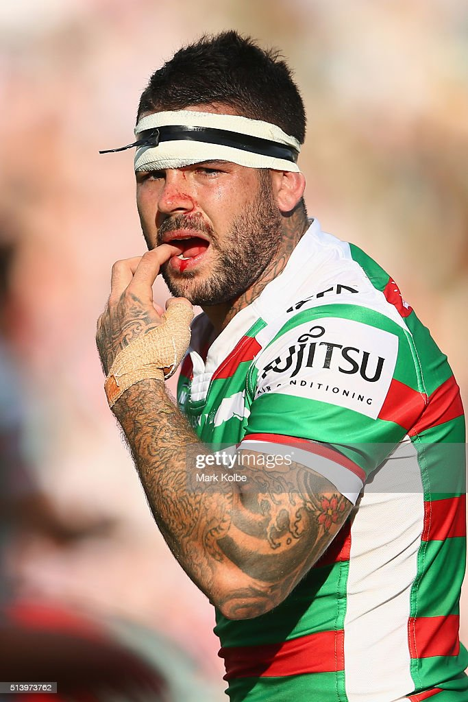 Adam Reynolds of the Rabbitohs feels his teeth after a heavy head knock during the round one NRL match between the Sydney Roosters and the South Sydney Rabbitohs at Allianz Stadium on March 6, 2016 in Sydney, Australia.