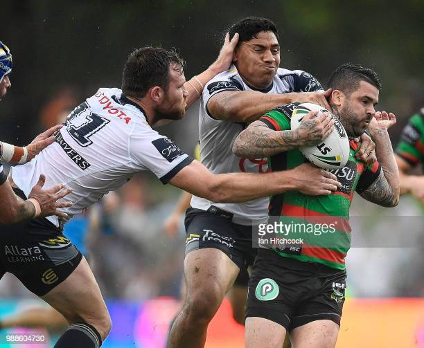 Adam Reynolds of the Rabbitohs is tackled by Jason Taumalolo and Gavin Cooper of the Cowboys during the round 16 NRL match between the South Sydney...