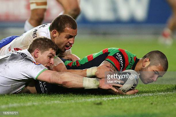 Adam Reynolds of the Rabbitohs is tackled just short of the line by Glen Buttriss and Blake Ferguson of the Raiders during the NRL Semi Final match...