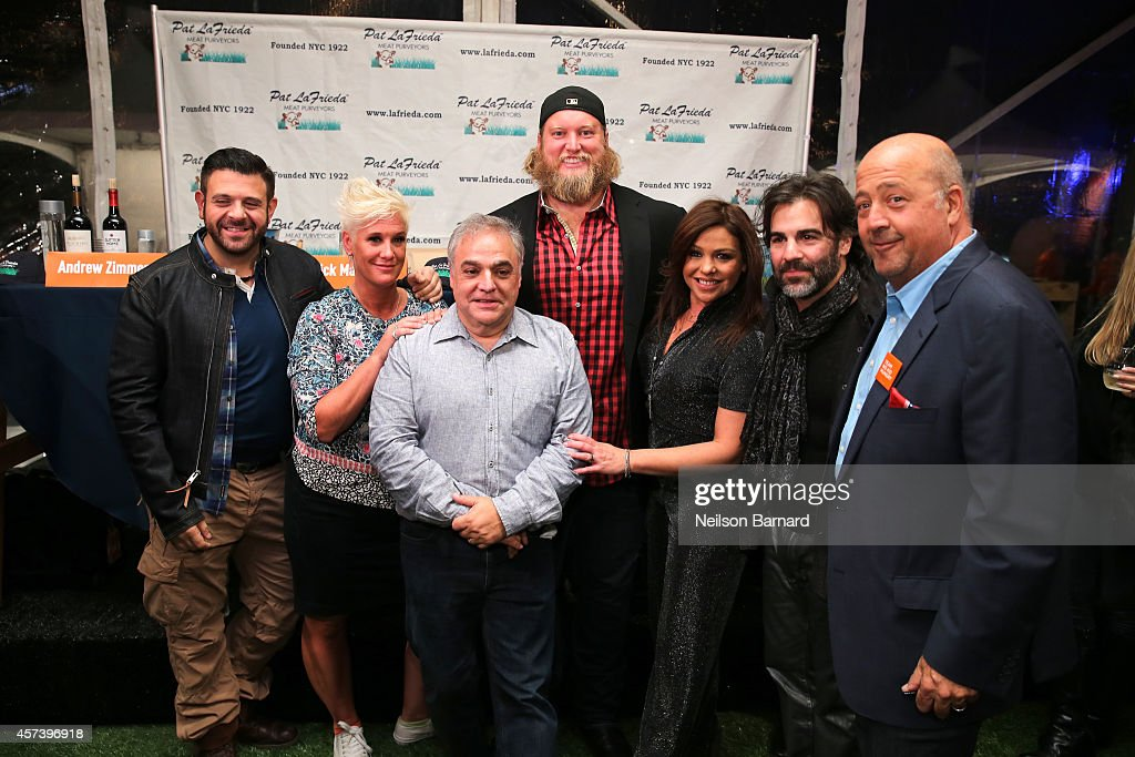 Adam Richman, Anne Burrell, Lee Brian Schrager, Nick Mangold, Rachael Ray, John Cusimano and Andrew Zimmern pose in front of the judges table at the Blue Moon Burger Bash presented by Pat LaFrieda Meats hosted by Rachael Ray during the Food Network New York City Wine & Food Festival Presented By FOOD & WINE at Esurance Rooftop Pier 92 on October 17, 2014 in New York City.