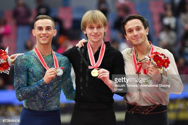 Adam Rippon of the USA Sergei Voronov of Russia and Alexei Bychenko of Israel pose on the podium in the medal ceremony during the ISU Grand Prix of...