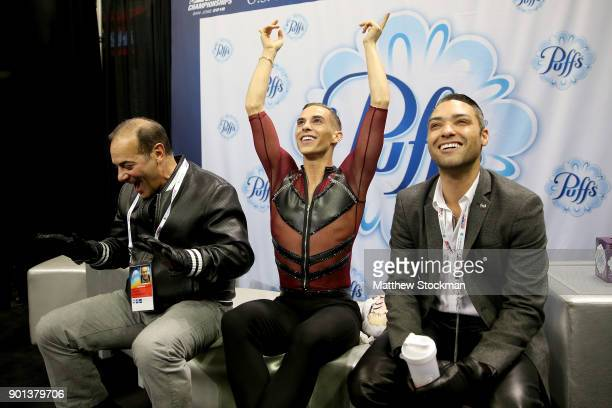 Adam Rippon reacts to his score in the kiss and cry with his coaches Rafael Arutunian and Derrick Delmore after skating in the Men's Short Program...