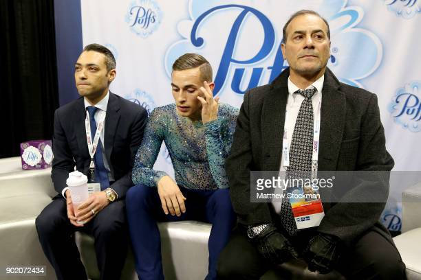 Adam Rippon waits for his score in the kiss and cry with his coaches Derrick Delmore and Rafael Arutunian after skating in the Men's Free Skate...