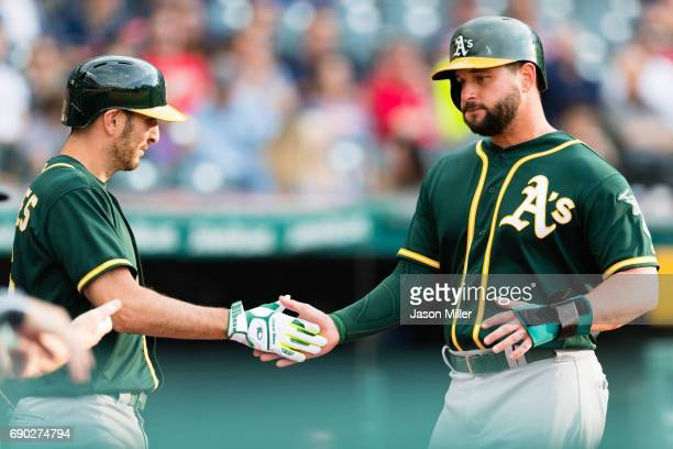 Adam Rosales celebrates with Yonder Alonso of the Oakland Athletics after Alonso scored on a sacrifice fly by Matt Joyce during the fourth inning...