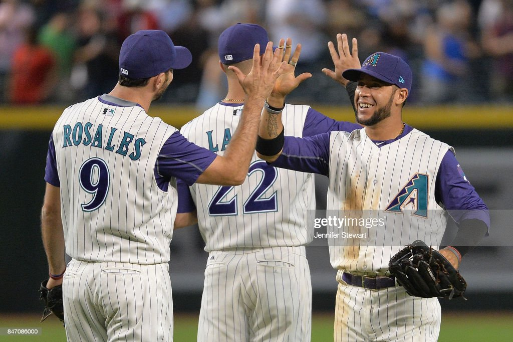 Adam Rosales #9, Jake Lamb #22 and Gregor Blanco #5 of the Arizona Diamondbacks celebrate after closing out the MLB game against the Colorado Rockies at Chase Field on September 14, 2017 in Phoenix, Arizona.