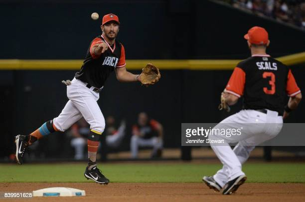 Adam Rosales of the Arizona Diamondbacks tosses the ball to Daniel Descalso to turn the double play against the San Francisco Giants in the fourth...
