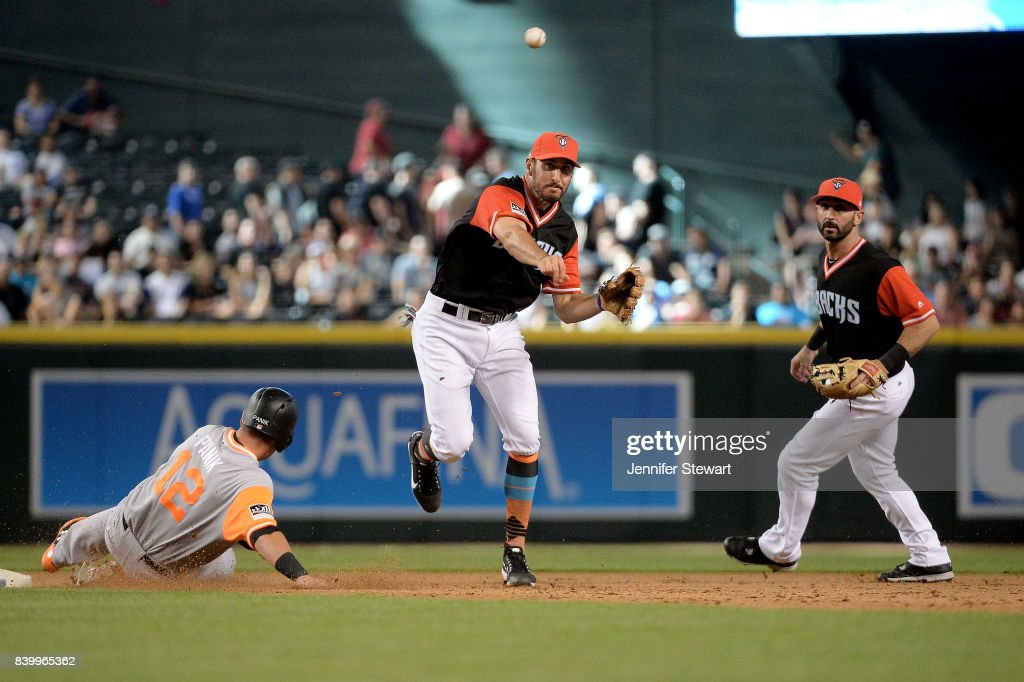 Adam Rosales #9 of the Arizona Diamondbacks turns the double play over the sliding Joe Panik #12 of the San Francisco Giants in the eighth inning against the San Francisco Giants at Chase Field on August 27, 2017 in Phoenix, Arizona.
