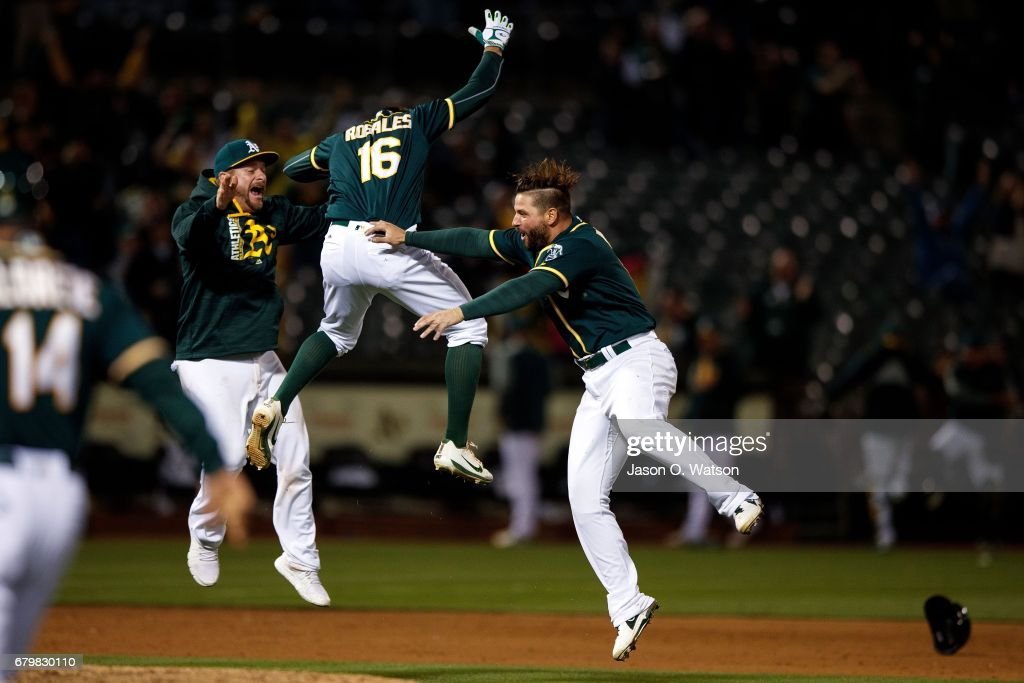 Adam Rosales #16 of the Oakland Athletics celebrates with Yonder Alonso #17 and Stephen Vogt #21 after hitting a two-run walk off single against the Detroit Tigers during the ninth inning at the Oakland Coliseum on May 6, 2017 in Oakland, California. The Oakland Athletics defeated the Detroit Tigers 6-5.