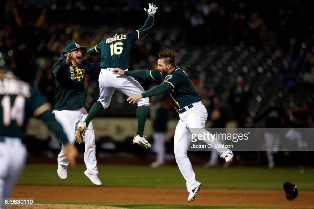 Adam Rosales of the Oakland Athletics celebrates with Yonder Alonso and Stephen Vogt after hitting a tworun walk off single against the Detroit...