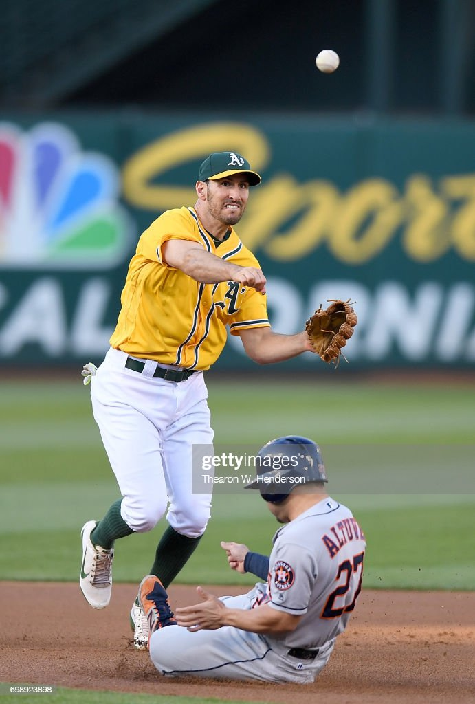 Adam Rosales #16 of the Oakland Athletics completes the double-play throwing over the top of Jose Altuve #27 of the Houston Astros in the top of the first inning at Oakland Alameda Coliseum on June 20, 2017 in Oakland, California.