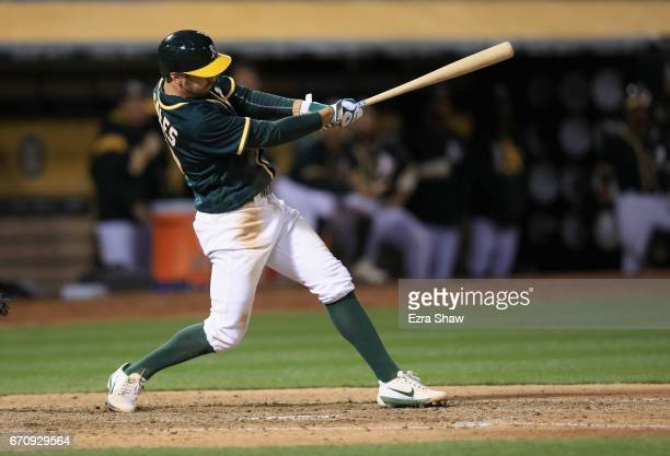 Adam Rosales of the Oakland Athletics hits a sacrifice fly that scored Rajai Davis in the fifth inning against the Seattle Mariners at Oakland...