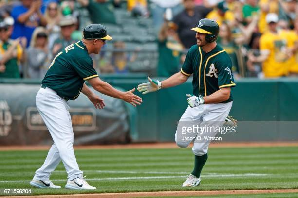 Adam Rosales of the Oakland Athletics is congratulated by third base coach Chip Hale after hitting a home run against the Seattle Mariners during the...