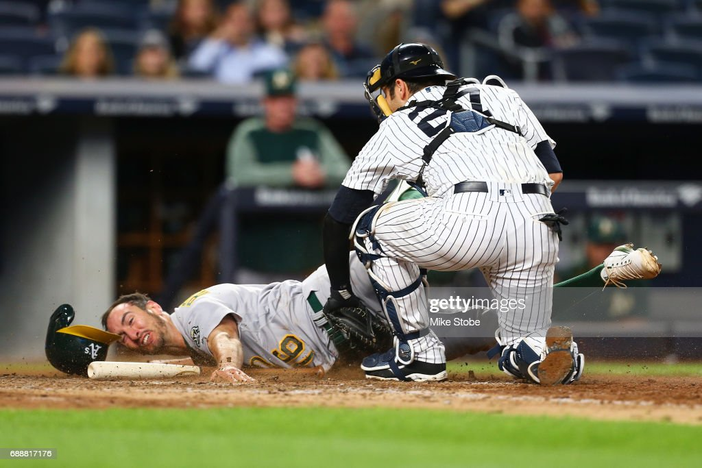 Adam Rosales #16 of the Oakland Athletics is tagged out at home plate by Austin Romine #27 of the New York Yankees in the eighth inning at Yankee Stadium on May 26, 2017 in the Bronx borough of New York City.