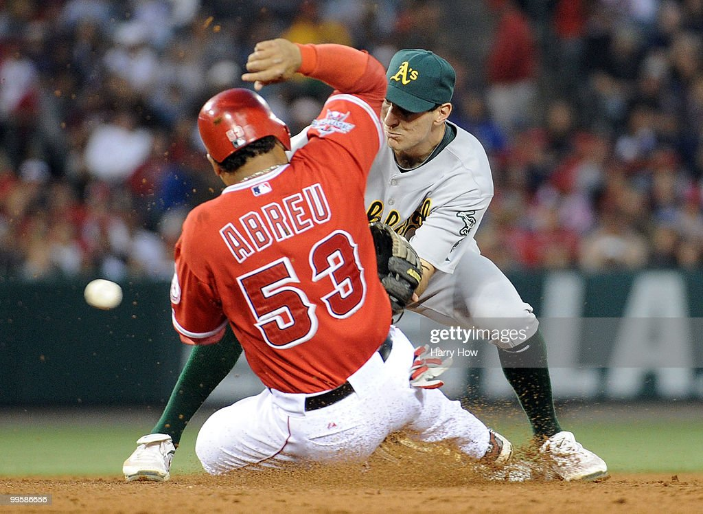 Adam Rosales #7 of the Oakland Athletics misses the throw from Landon Powell #35 allowing Bobby Abreu #53 to steal second base and Howie Kendrick #47 of the Los Angeles Angels to score a run during the fifth inning at Angels Stadium on May 15, 2010 in Anaheim, California.