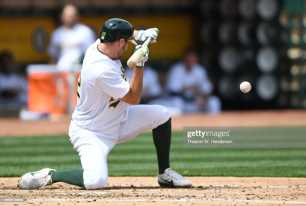 Adam Rosales #16 of the Oakland Athletics squeeze bunts to score Yonder Alonso #17 against the Houston Astros in the bottom of the second inning at Oakland Alameda Coliseum on April 15, 2017 in Oakland, California. All players are wearing #42 in honor of Jackie Robinson Day.