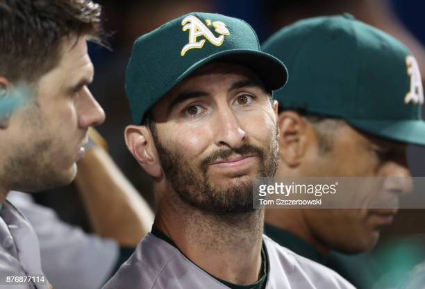 Adam Rosales of the Oakland Athletics talks to Josh Phegley in the dugout during MLB game action against the Toronto Blue Jays at Rogers Centre on...
