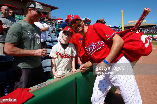 Adam Rosales of the Philadelphia Phillies poses for a picture with a fan before the spring training game against the Minnesota Twins at Spectrum...
