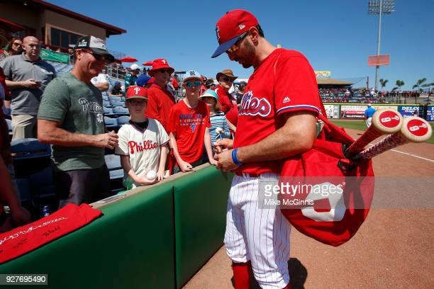 Adam Rosales of the Philadelphia Phillies signs some autographes before the spring training game against the Minnesota Twins at Spectrum Field on...