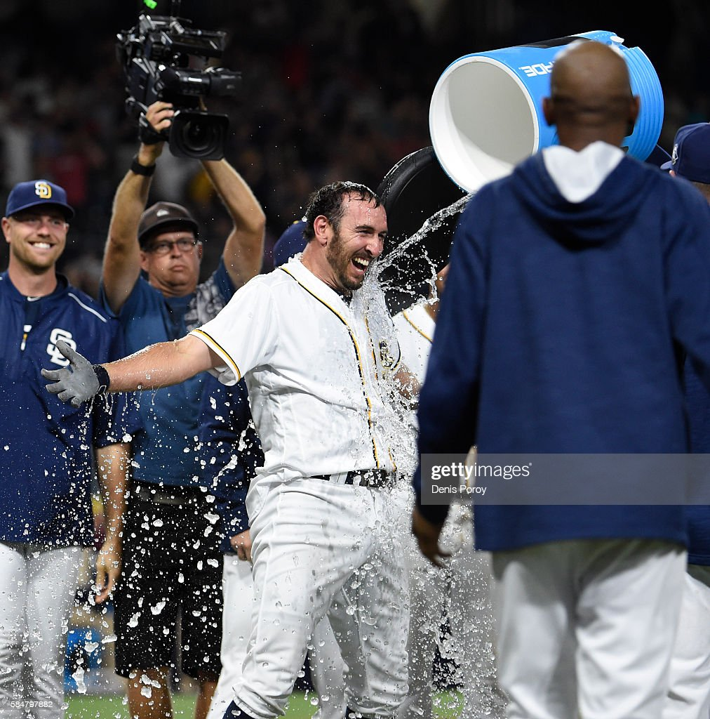 Adam Rosales #9 of the San Diego Padres celebrate with teammates after hitting a walk-off solo home run during the tenth inning of a baseball game against the Cincinnati Reds at PETCO Park on July 30, 2016 in San Diego, California. The Padres won 2-1.