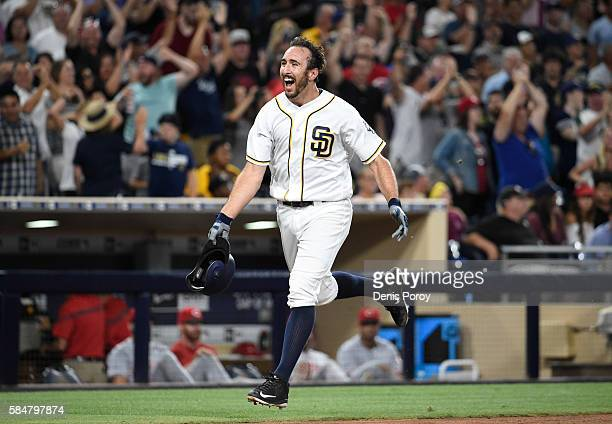 Adam Rosales of the San Diego Padres celebrates after hitting a walkoff solo home run during the tenth inning of a baseball game against the...
