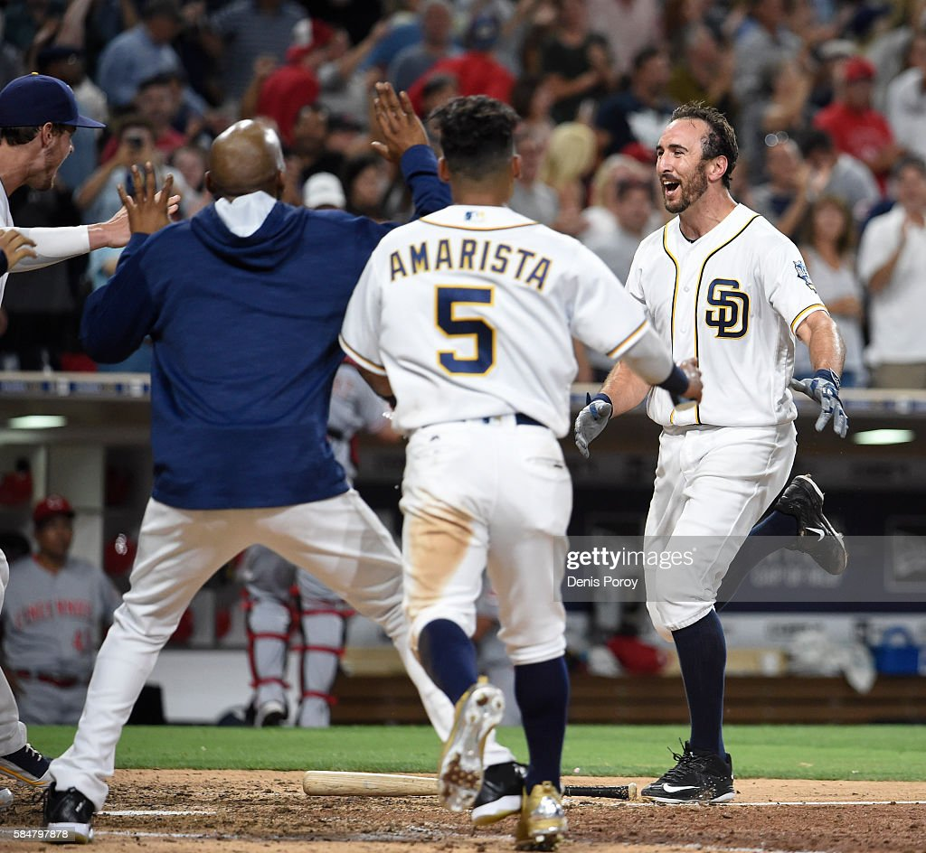 Adam Rosales #9 of the San Diego Padres, right, celebrates with teammates after hitting a walk-off solo home run during the tenth inning of a baseball game against the Cincinnati Reds at PETCO Park on July 30, 2016 in San Diego, California. The Padres won 2-1.