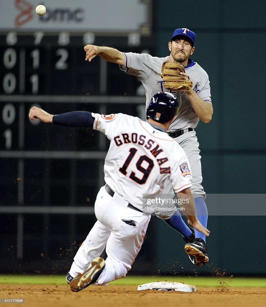 Adam Rosales #9 of the Texas Rangers turns a double play as Robbie Grossman #19 of the Houston Astros slides into second during the fifth inning at Minute Maid Park on May 4, 2015 in Houston, Texas.
