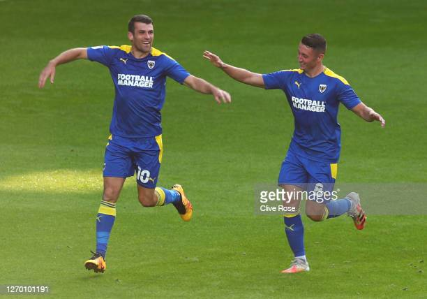Adam Roscrow of AFC Wimbledon celebrates after scoring his team's first goal with Anthony Hartigan during the EFL Trophy match AFC Wimbledon and...