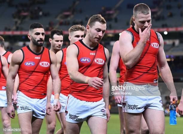 Adam Saad Devon Smith and Jake Stringer of the Bombers look dejected after losing the round 22 AFL match between the Richmond Tigers and the Essendon...