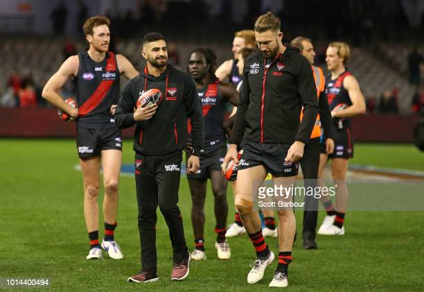Adam Saad of the Bombers and Cale Hooker of the Bombers leaves the field injured after the round 21 AFL match between the Essendon Bombers and the St...