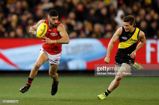 Adam Saad of the Bombers is chased by Liam Baker of the Tigers during the 2018 AFL round 22 match between the Richmond Tigers and the Essendon...