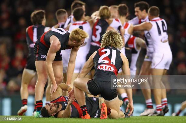 Adam Saad of the Bombers is helped on the ground by his teammates after a late hit by Nathan Brown of the Saints during the round 21 AFL match...