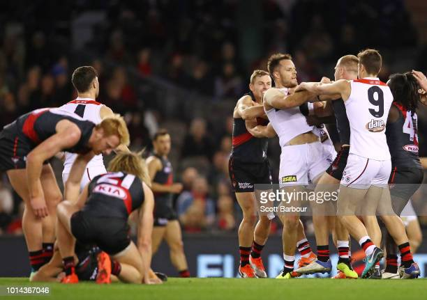 Adam Saad of the Bombers is helped on the ground by his teammates after a late hit by Nathan Brown of the Saints as players wrestle with Nathan Brown...