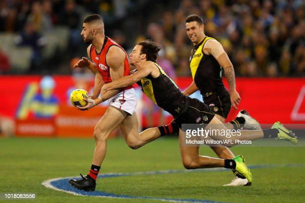 Adam Saad of the Bombers is tackled by Daniel Rioli of the Tigers in the dying seconds during the 2018 AFL round 22 match between the Richmond Tigers...