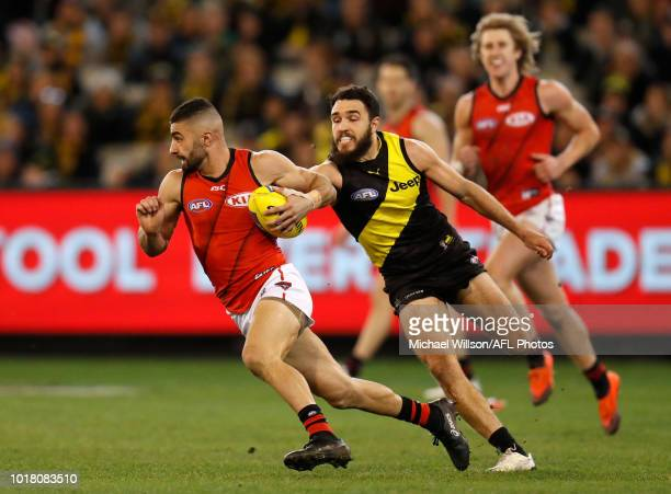 Adam Saad of the Bombers is tackled by Shane Edwards of the Tigers during the 2018 AFL round 22 match between the Richmond Tigers and the Essendon...