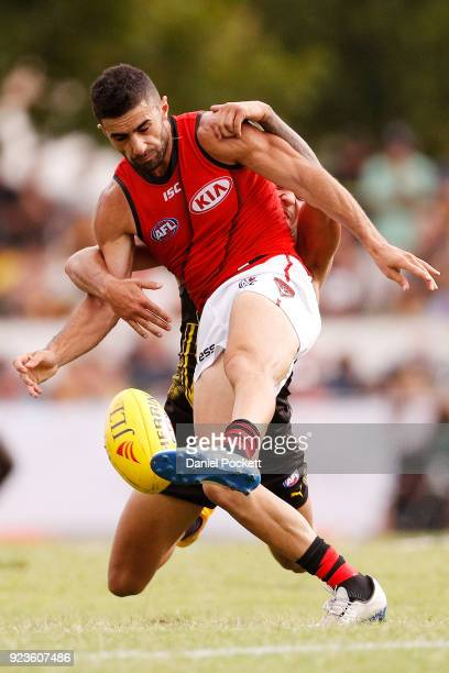 Adam Saad of the Bombers kicks the ball whilst being tackled during the JLT Community Series AFL match between the Essendon Bombers and the Richmond...