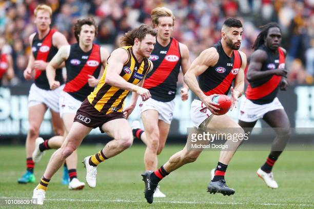 Adam Saad of the Bombers runs with the ball from Blake Hardwick of the Hawks during the round 20 AFL match between the Hawthorn Hawks and the...