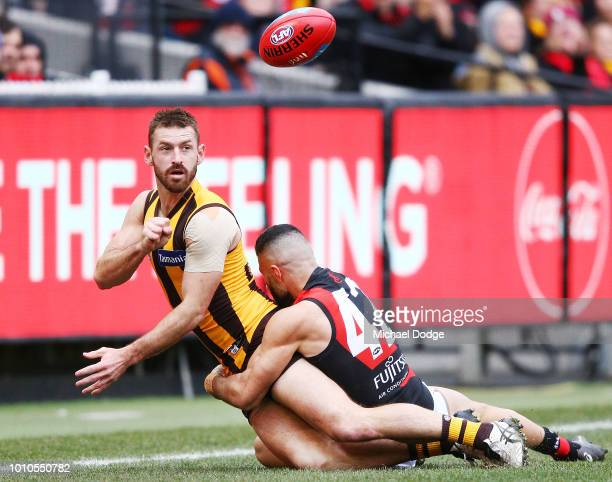 Adam Saad of the Bombers tackles Brendan Whitecross of the Hawks during the round 20 AFL match between the Hawthorn Hawks and the Essendon Bombers at...