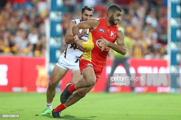 Adam Saad of the Suns runs the ball during the round three AFL match between the Gold Coast Suns and the Hawthorn Hawks at Metricon Stadium on April...