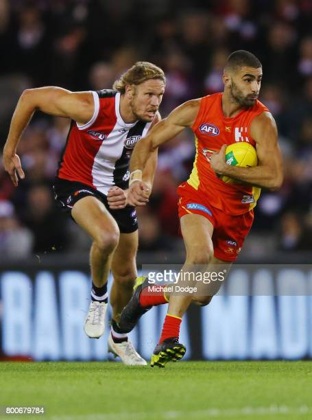 Adam Saad of the Suns runs with the ball away from Sam Gilbert of the Saints during the round 14 AFL match between the St Kilda Saints and the Gold...