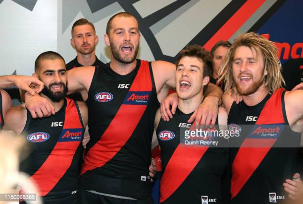 Adam Saad, Tom Bellchambers, Zach Merrett and Dyson Heppell of the Bombers sing the song in the rooms after winning the round nine AFL match between...